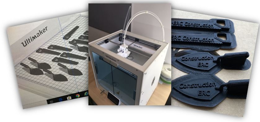 The image shows a 3D printer and small key rings and tokens which have been made for open events and competitions.